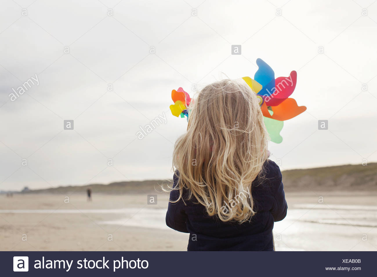 Rear view of girl with paper windmills on beach, Bloemendaal aan Zee, Netherlands - Stock Image