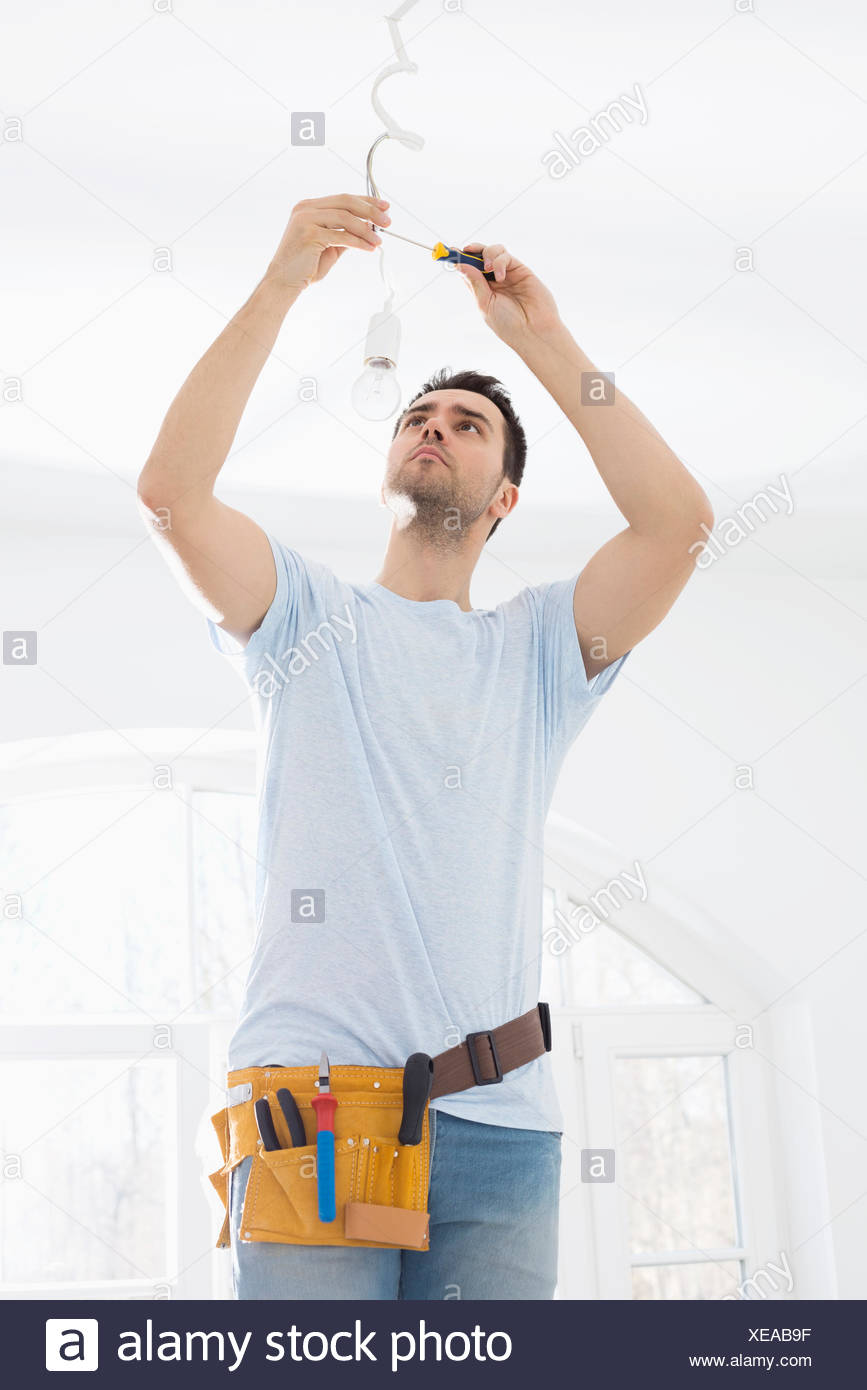 Mid-adult man fixing light bulb wiring in new house - Stock Image