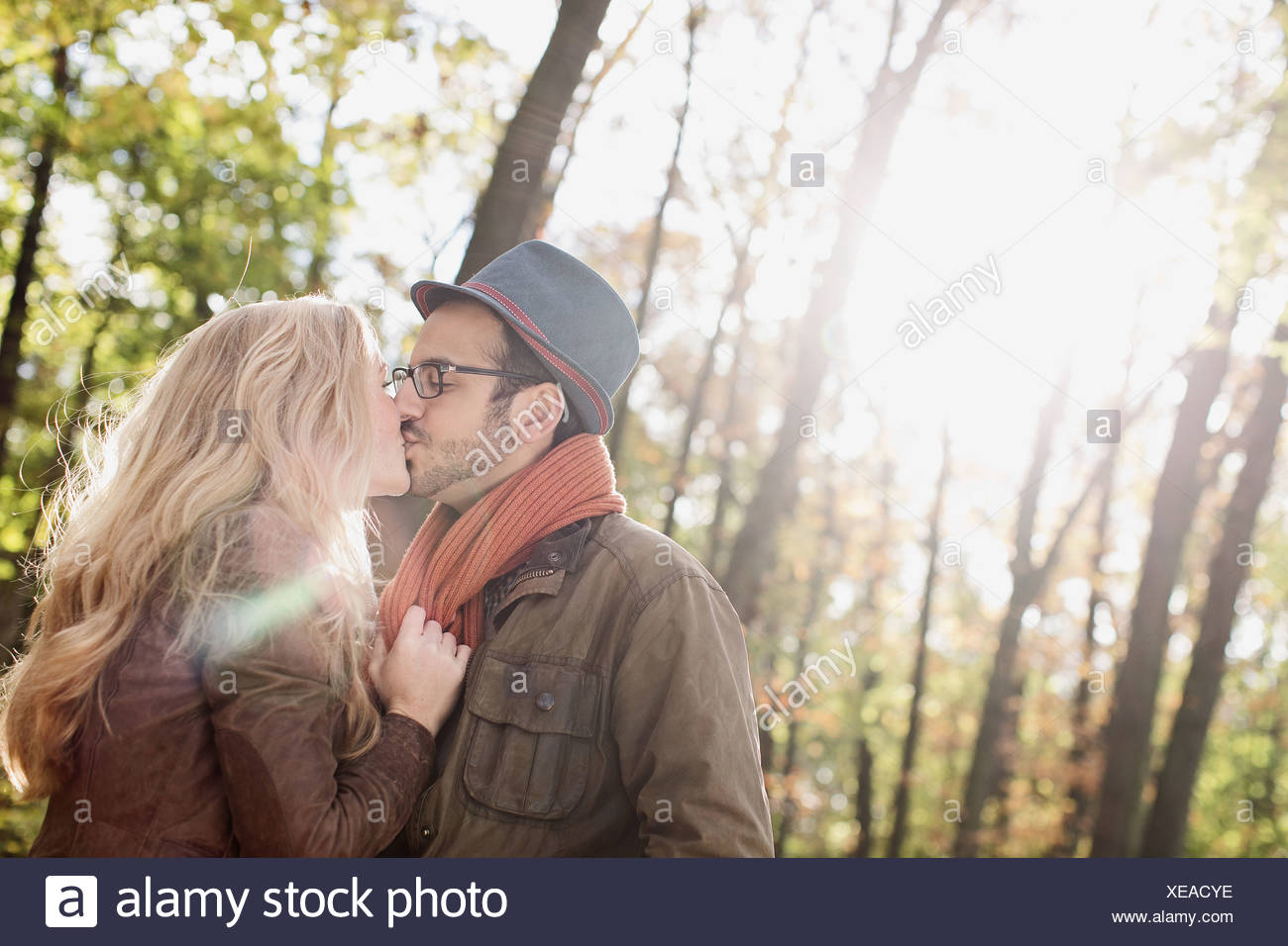 Smiling couple kissing in forest - Stock Image
