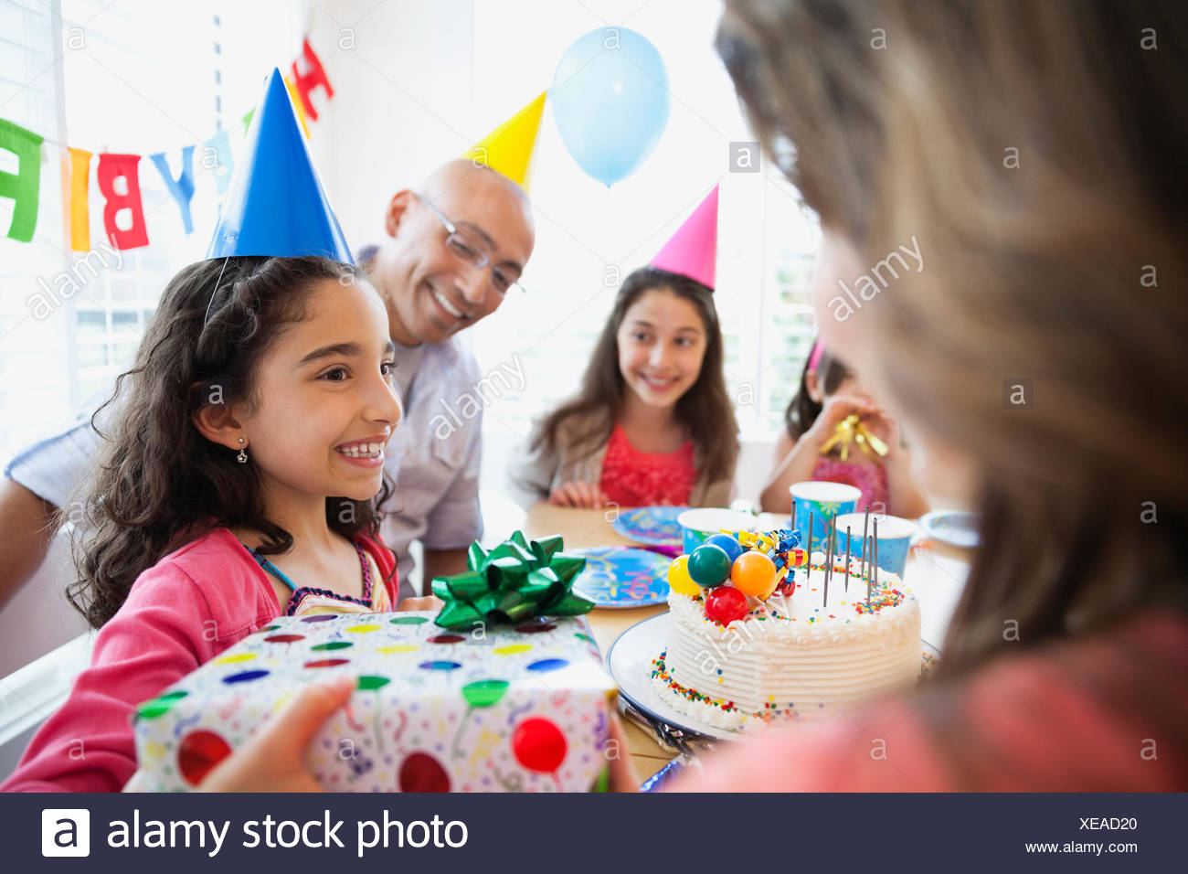 Birthday girl holding gift with family looking at her - Stock Image