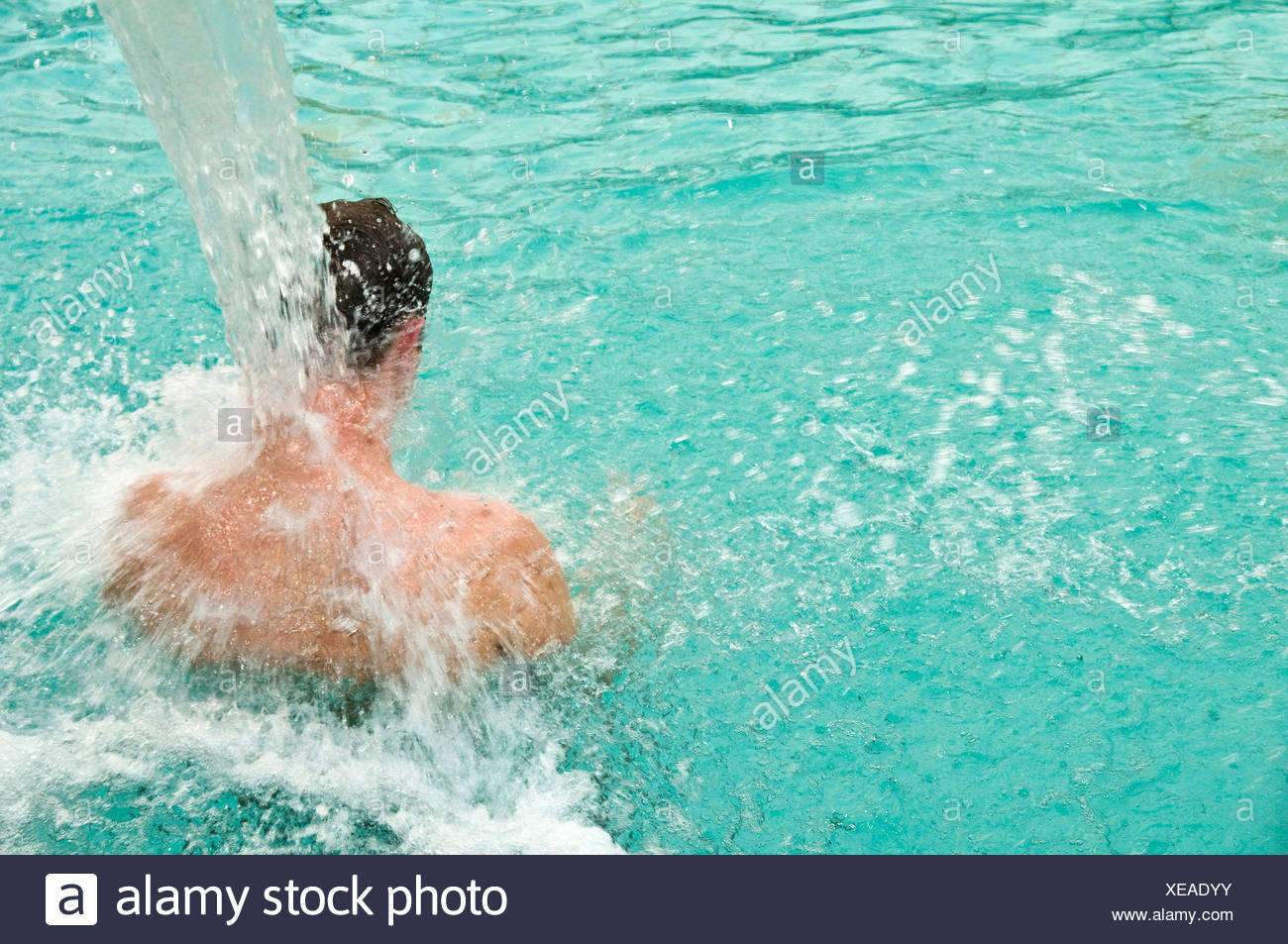 Man in swimming pool from behind with massaging jet of water Stock ...