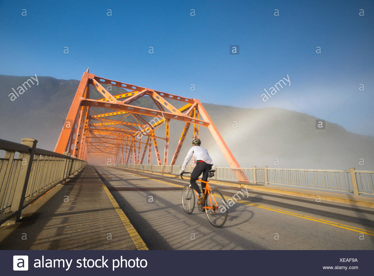 A man rides his road bike on the commute while a brockenspectre shines behind him in Nelson, BC - Stock Image