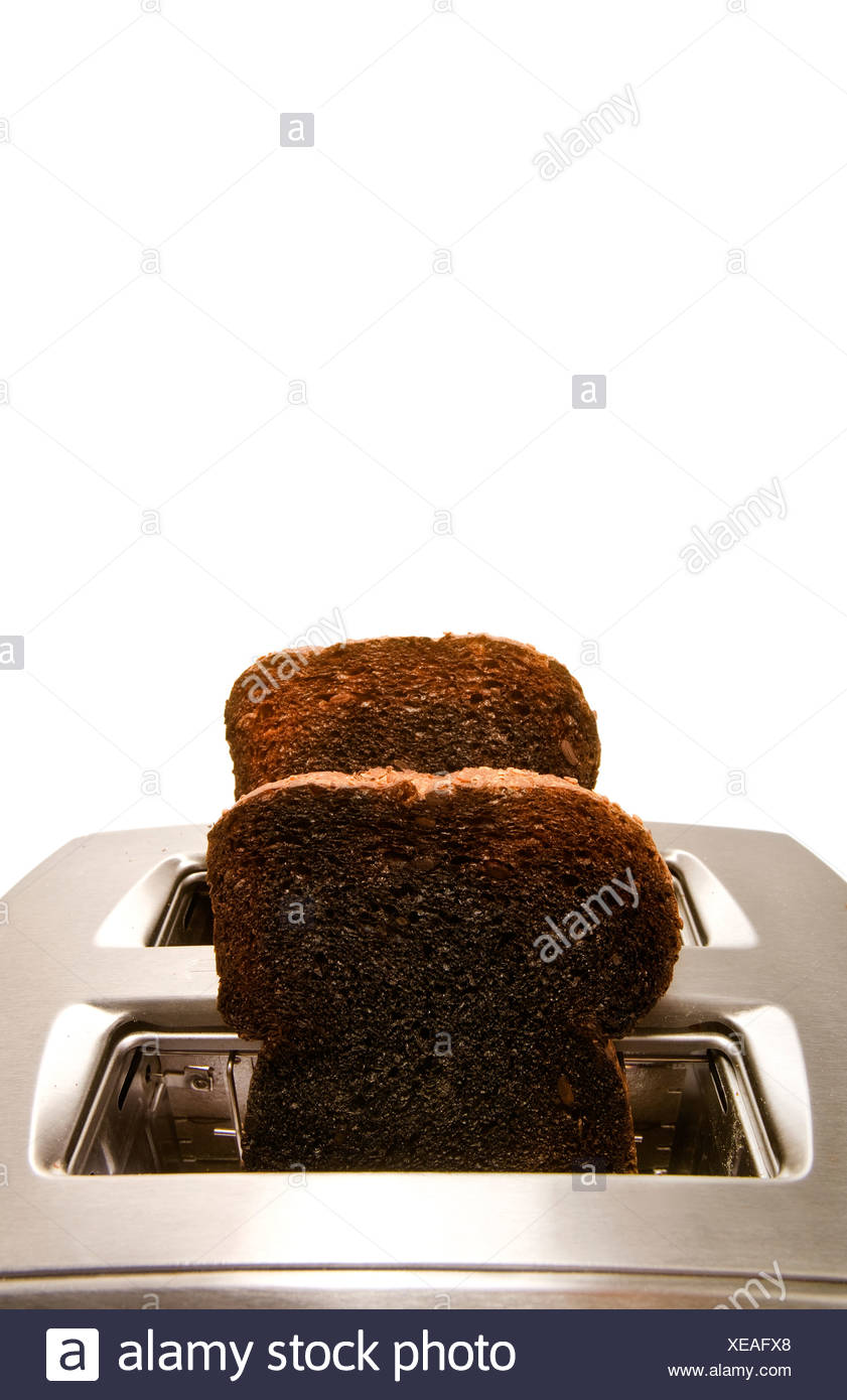 Burnt toast popping out of a toaster - Stock Image