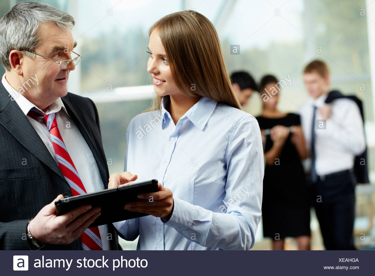 Young woman talking to a senior businessman - Stock Image