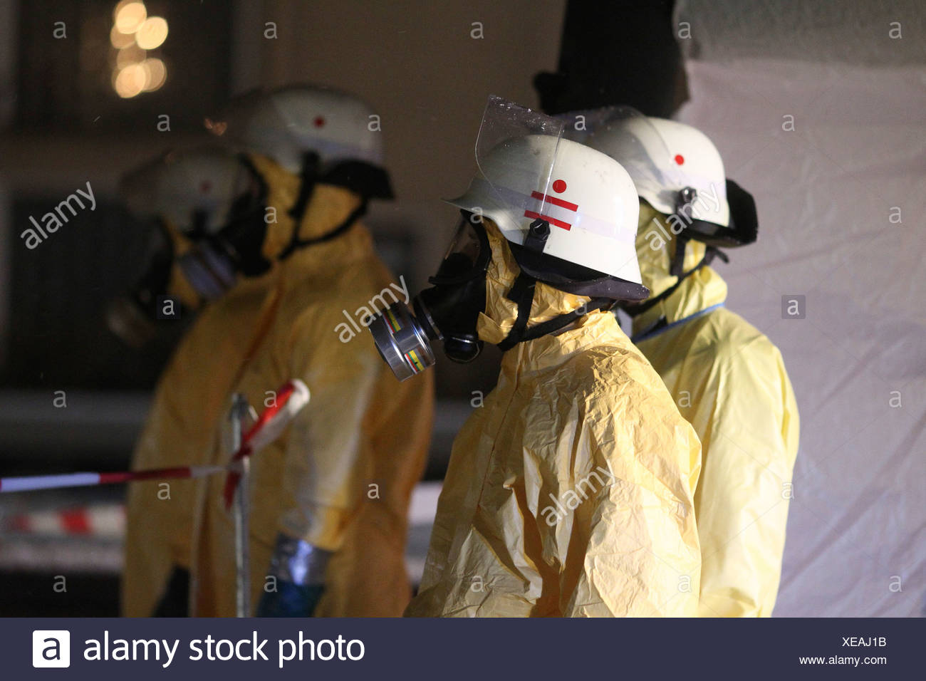 Firefighters equipped for containment of a hazardous substances wearing protective clothing, helmets and respirator masks - Stock Image