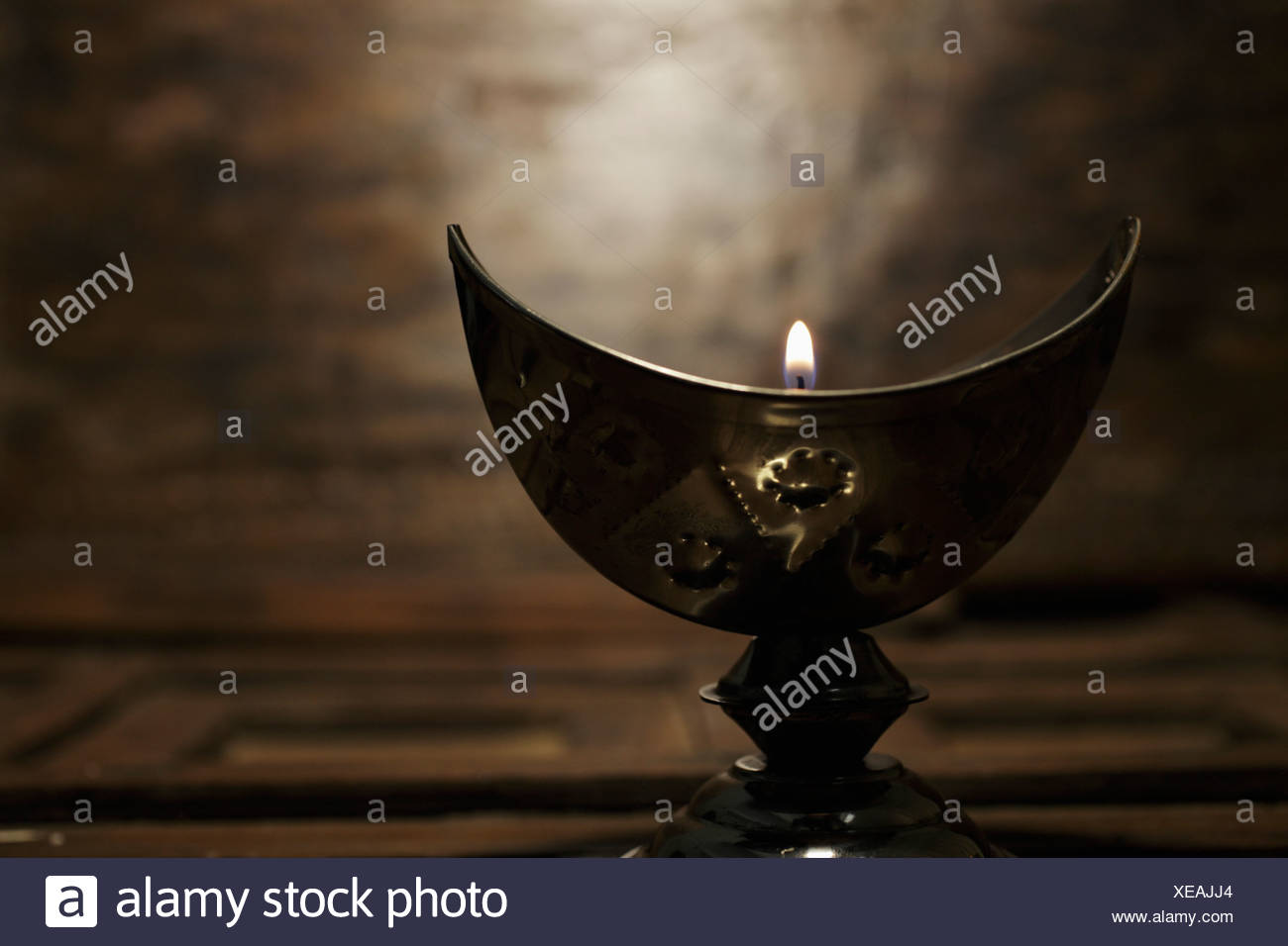 Silver cresent candle holder with lit candle - Stock Image