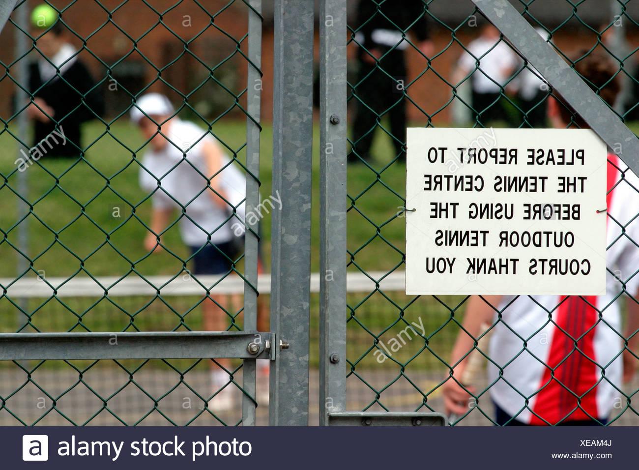 Schoolchildren playing tennis Weybridge Surrey UK - Stock Image