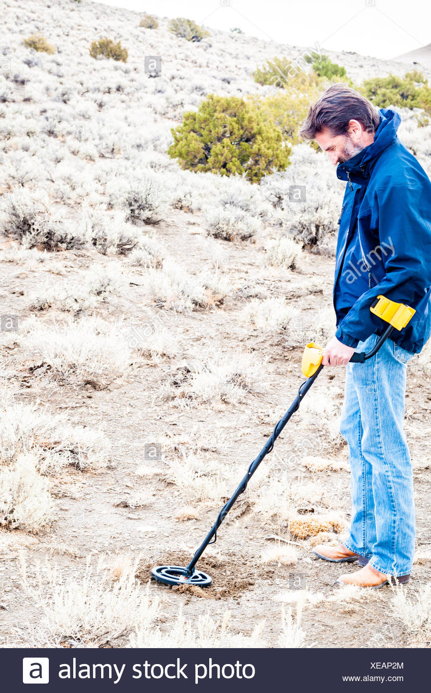 Man using metal detector in Black Rock desert, Nevada, America, USA Stock Photo