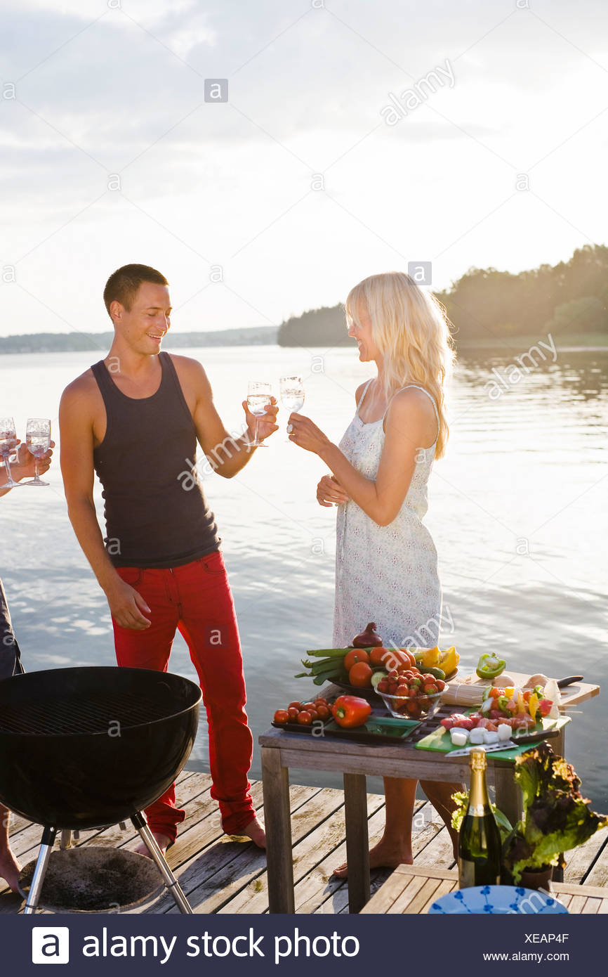 Couple standing on jetty toasting with glasses Stock Photo
