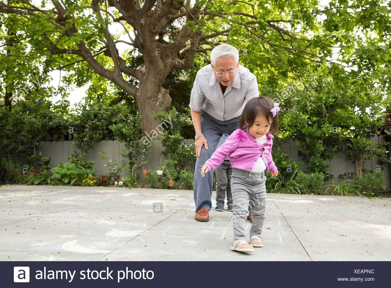 Grandfather playing hopscotch with toddler granddaughter - Stock Image