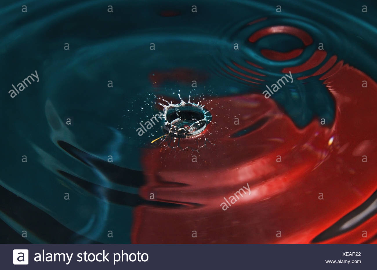 a drop of water hitting a surface of water - Stock Image