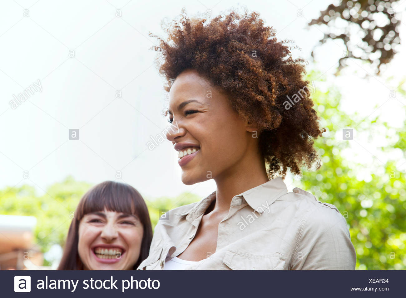 Portrait of young woman laughing with afro hairstyle - Stock Image