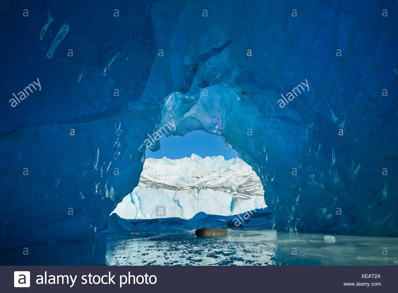 View from inside an ice cave of an iceberg frozen in Mendenhall Lake, Juneau, Southeast Alaska, Winter - Stock Image