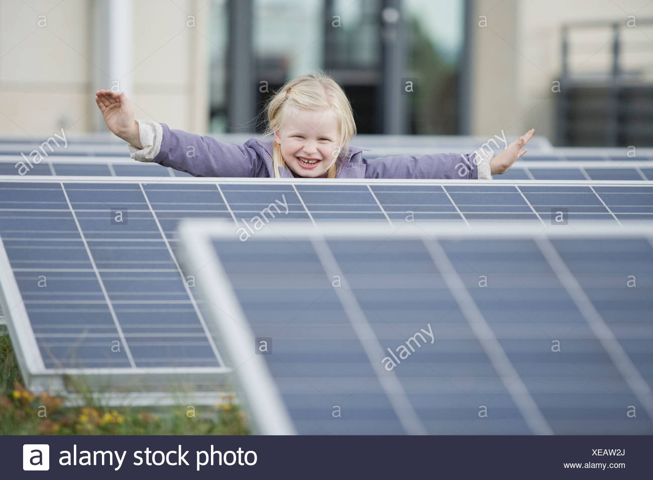 A young girl standing amongst solar panels - Stock Image