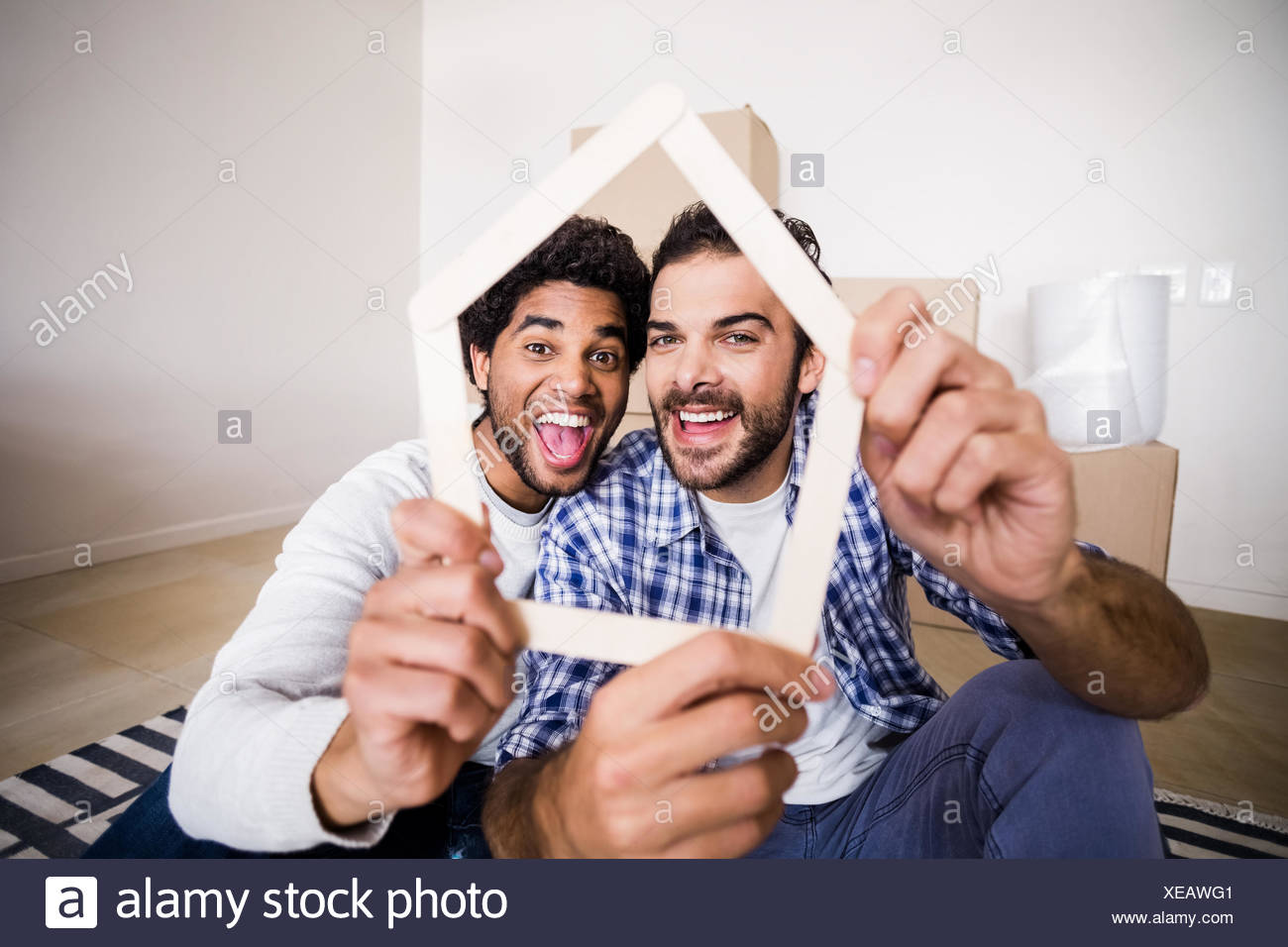 Happy gay couple holding house outline - Stock Image