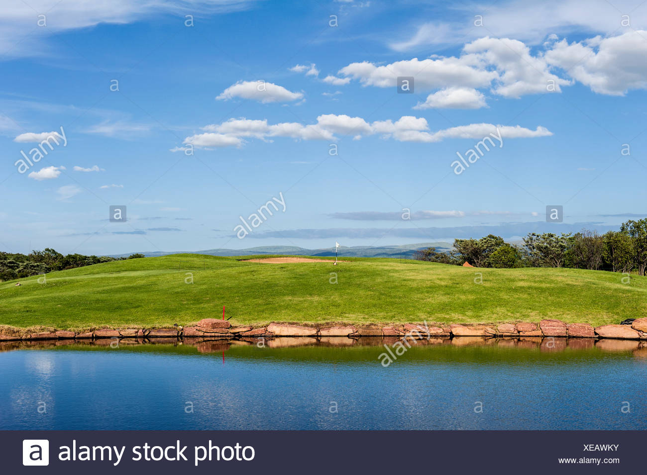 Morning view of a golf fairway and putting green beside a water trap. - Stock Image