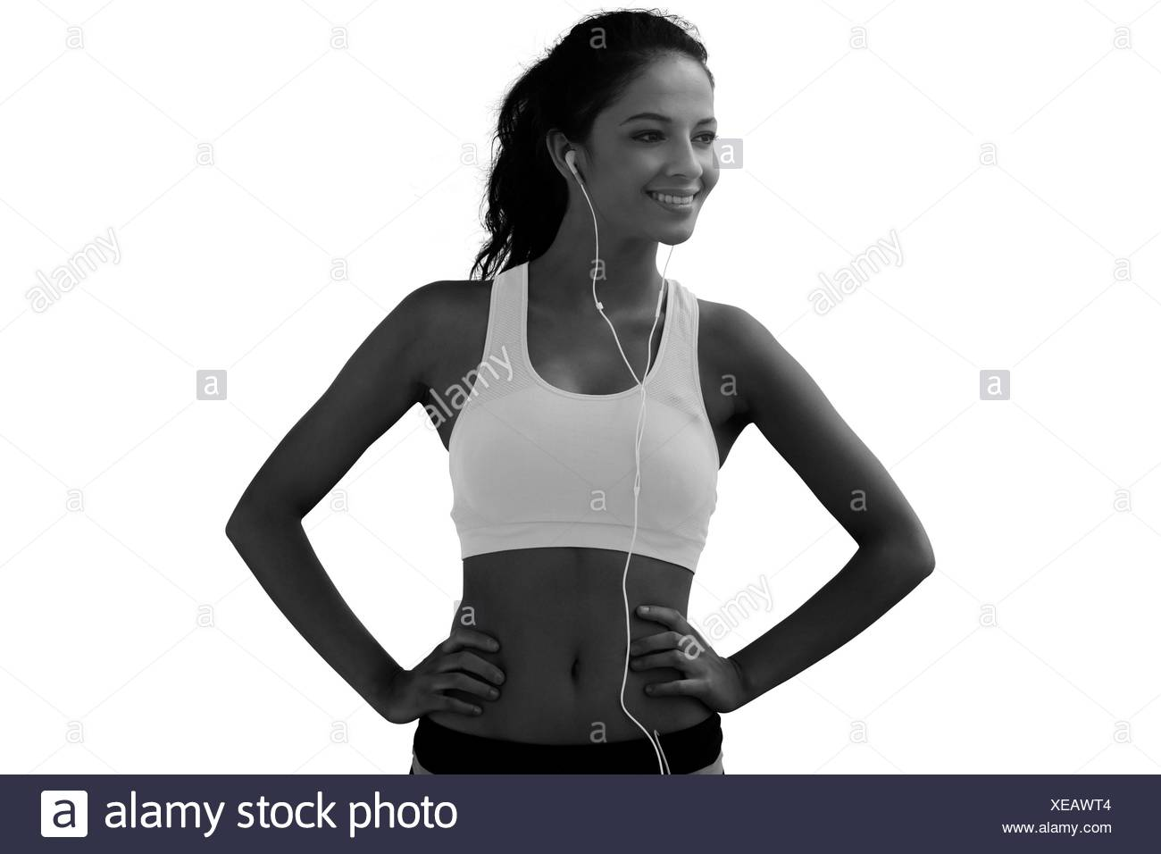 Composite image of beautiful smiling healthy with earphones on beach - Stock Image