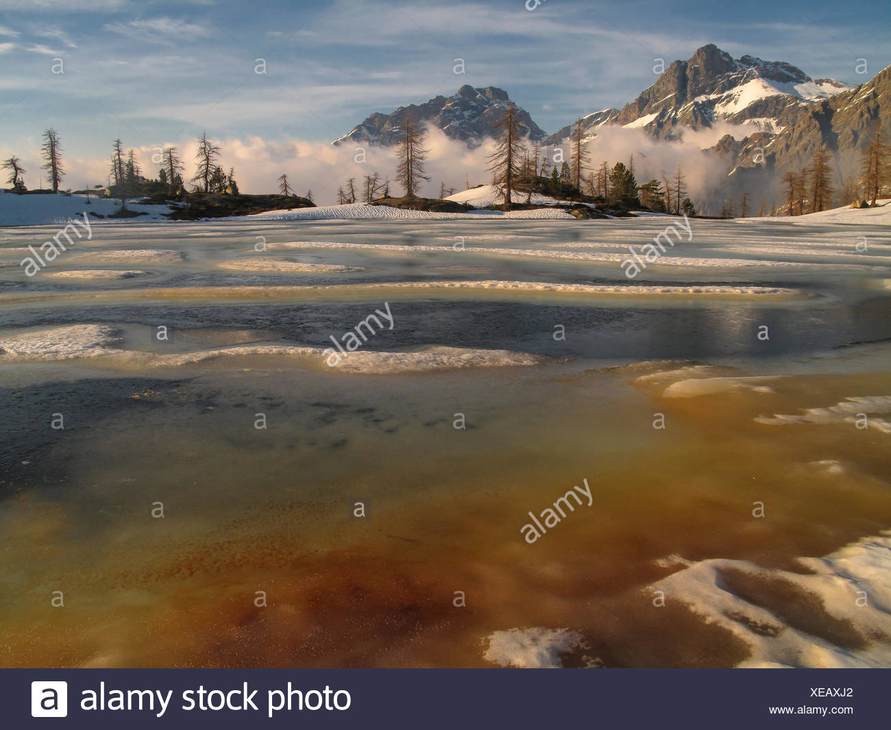 Vallette lake in sping, melting snow and ice, red algae on the ice, Mont Avic Natural Park, Aosta Valley, Italy - Stock Image