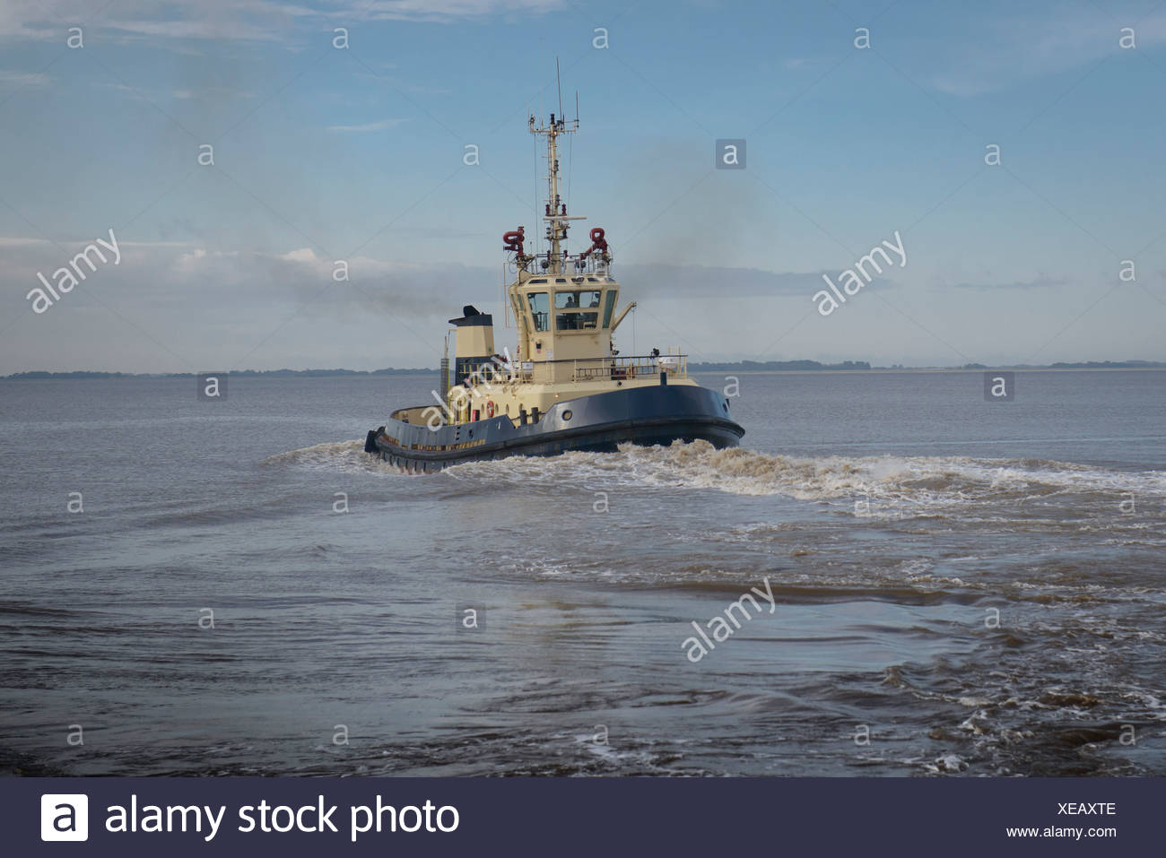Tugboat sailing in water - Stock Image