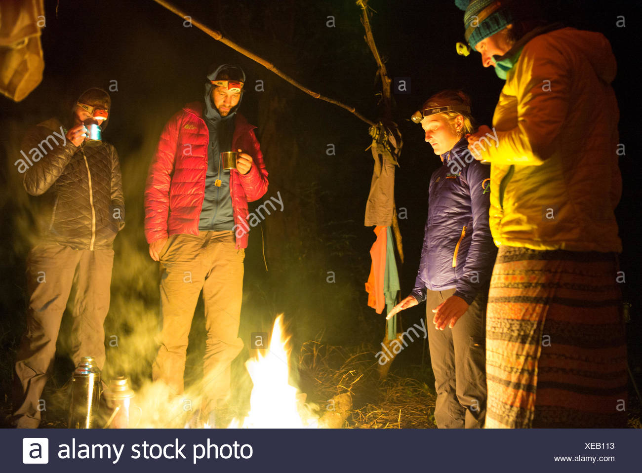 Expedition members stand around a blazing campfire. - Stock Image