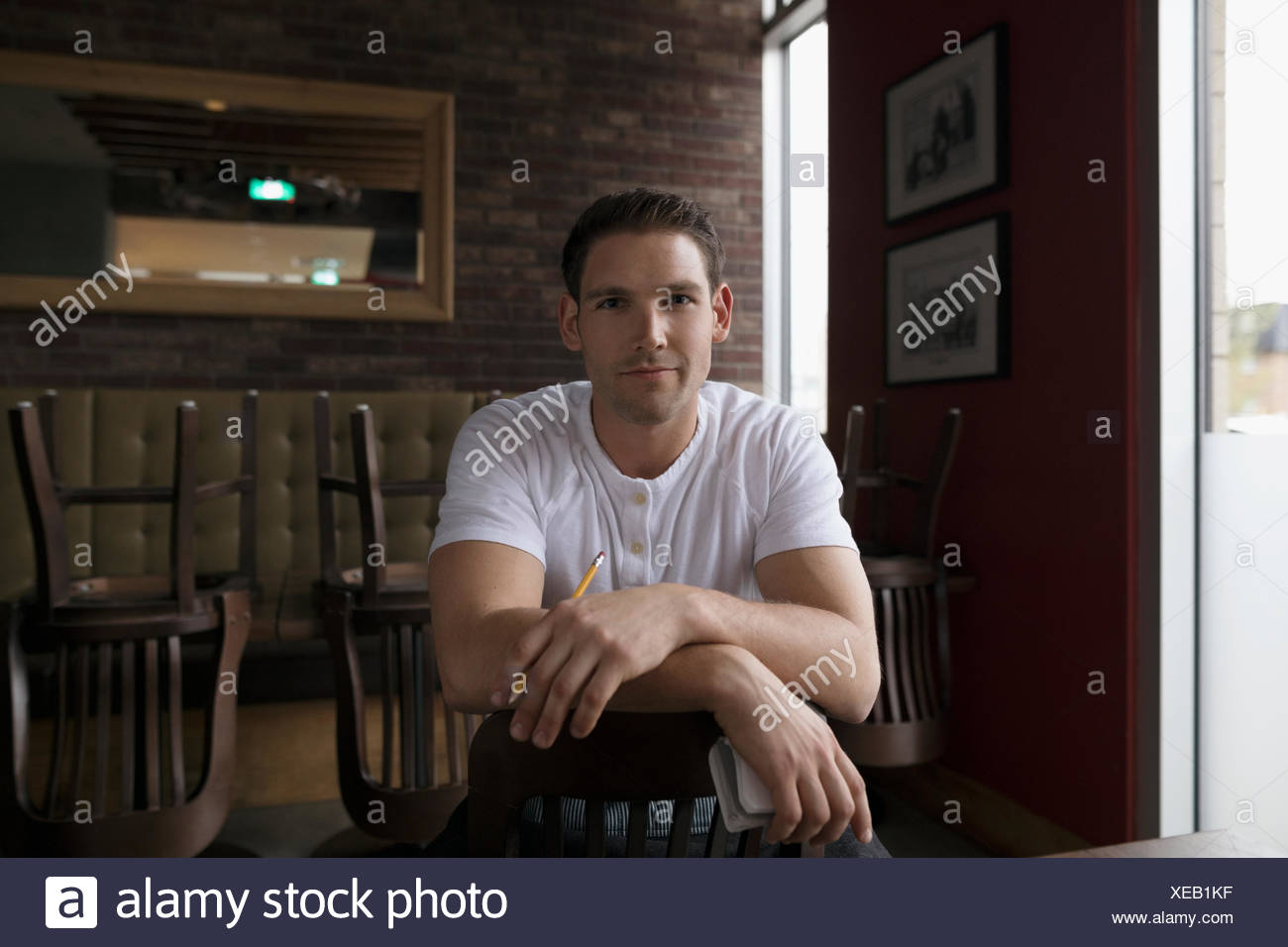 Portrait confident waiter straddling chair in diner - Stock Image