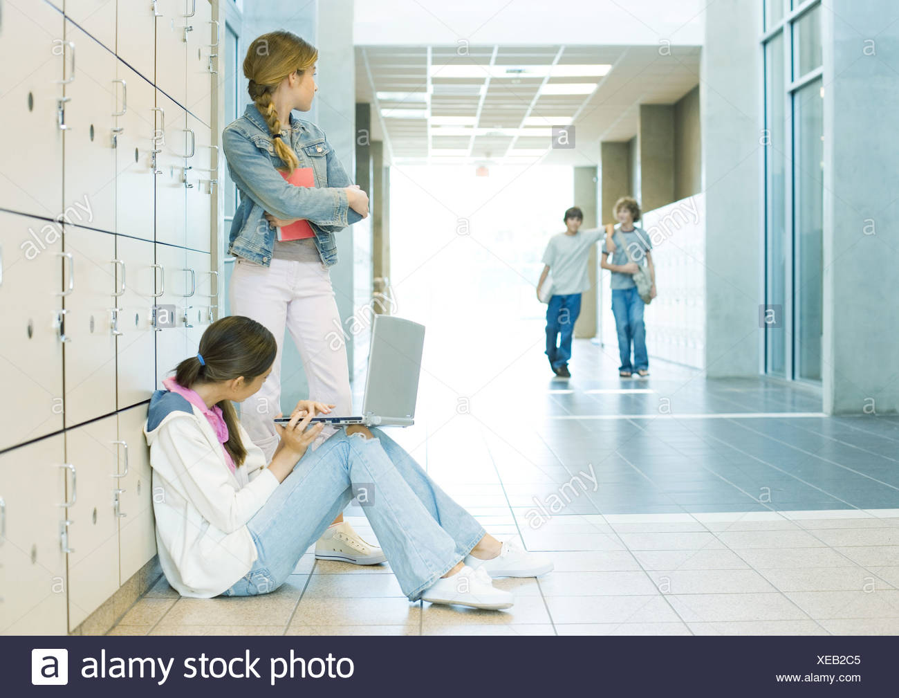 Two high school girls by lockers, watching teen boys approaching - Stock Image