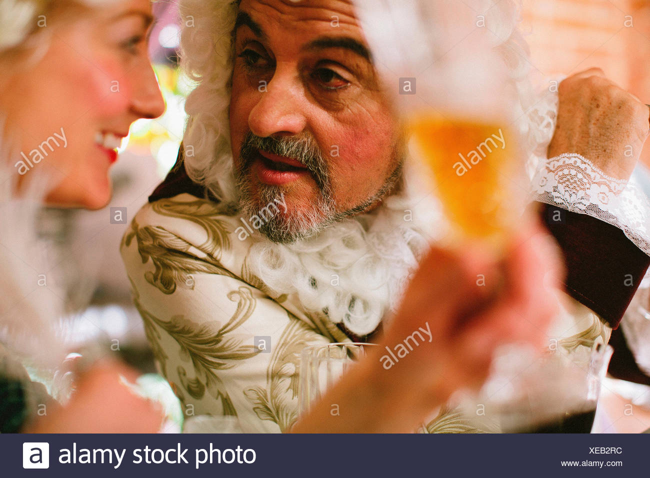 Man talks with woman during Victorian themed dinner. - Stock Image