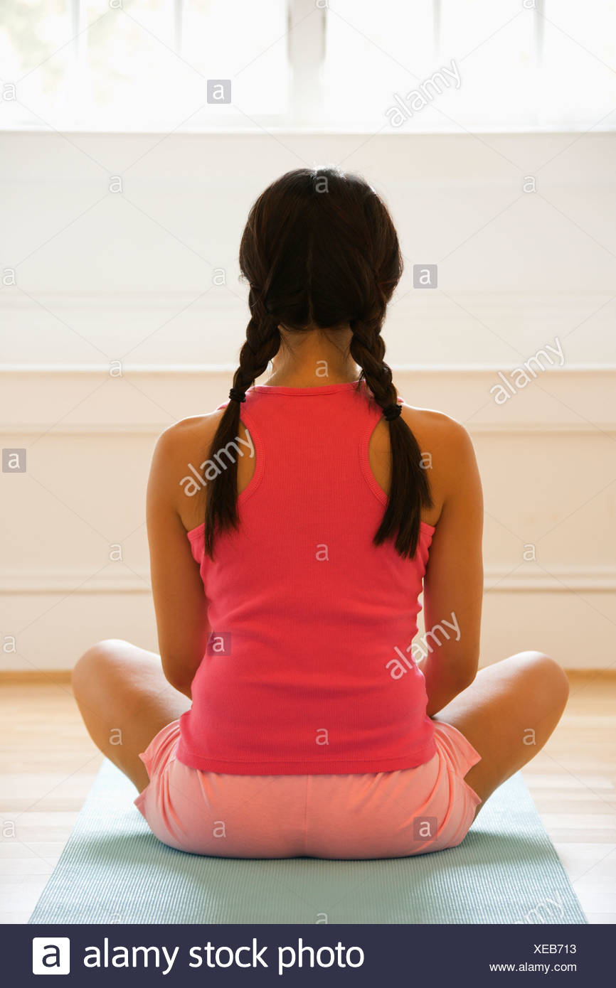 Rear view of young woman sitting on mat with legs crossed in yoga pose - Stock Image
