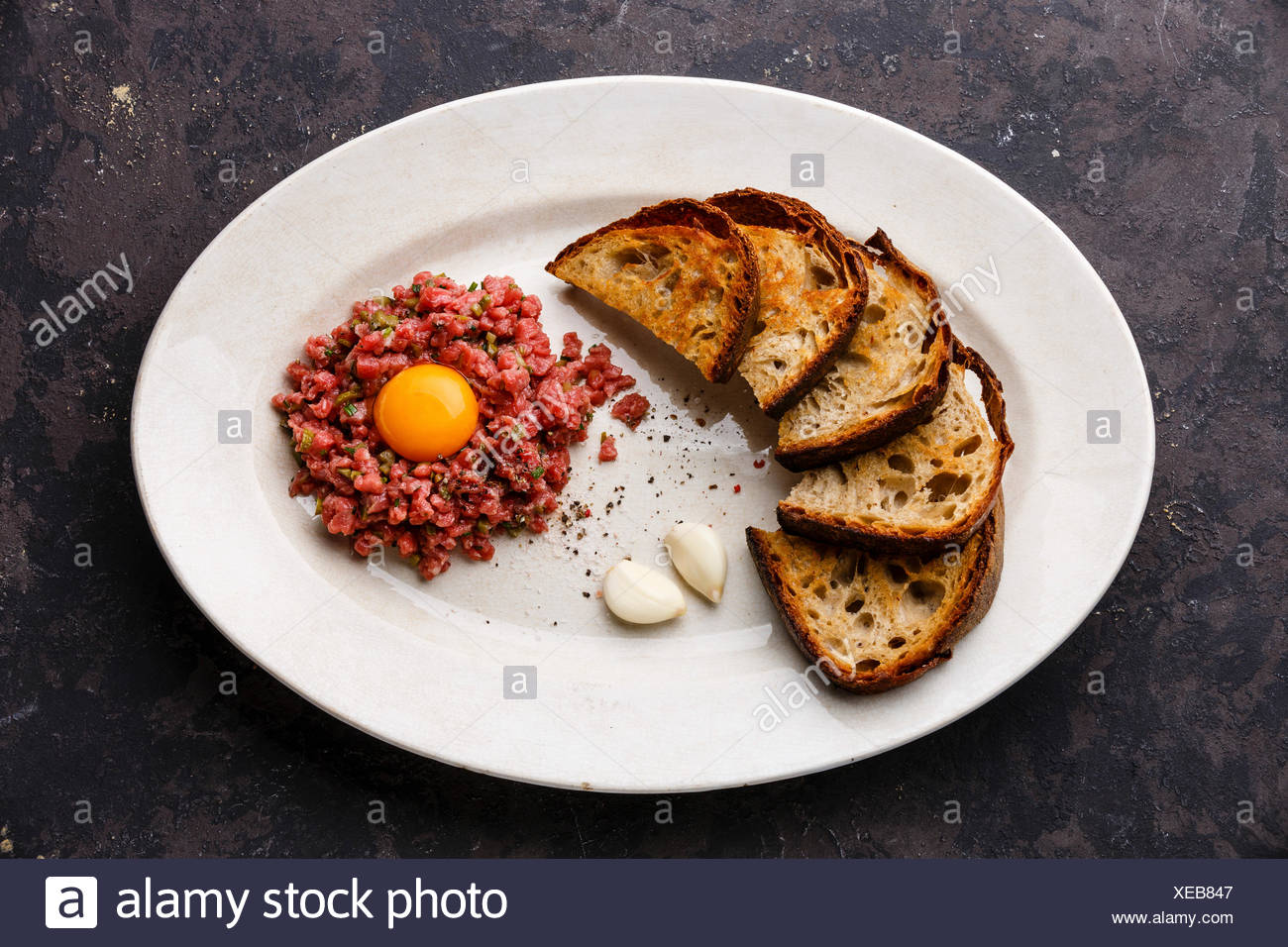 Beef tartare with pickled cucumber and toasts on white plate on dark background - Stock Image