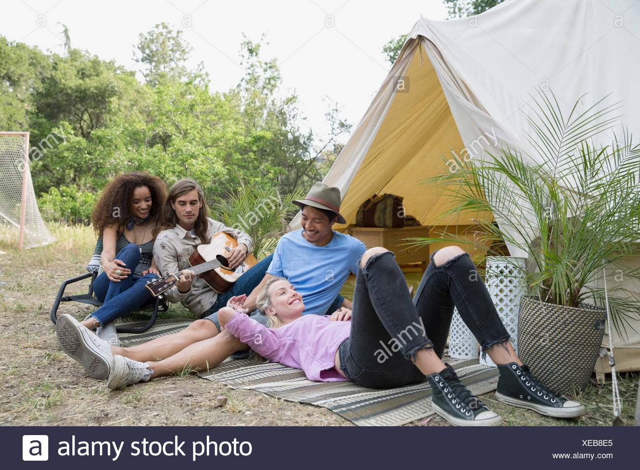 Young friends relaxing playing guitar outside camping yurt - Stock Image