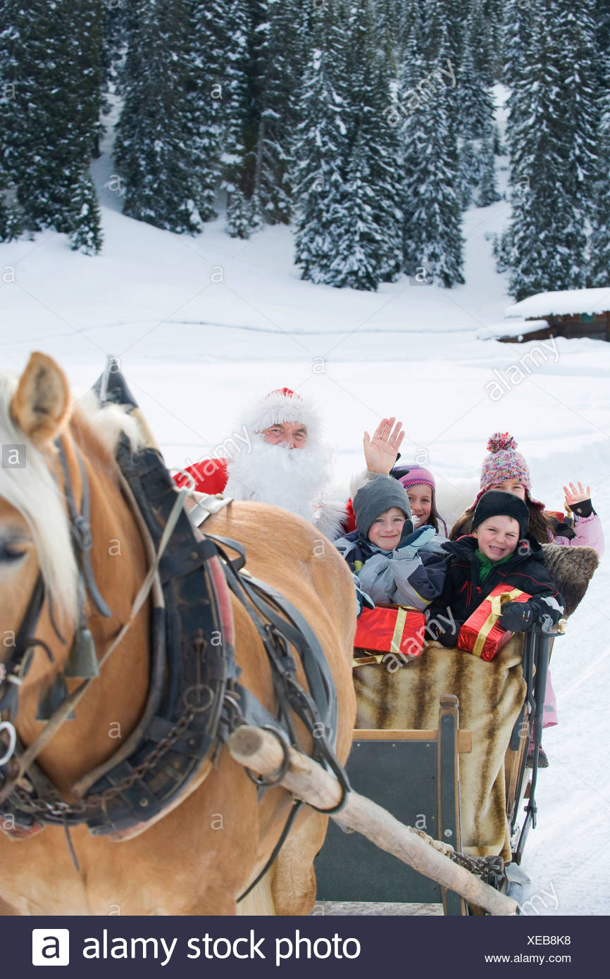 Italy, South Tyrol, Seiseralm, Santa Claus and children taking a sleigh ride - Stock Image