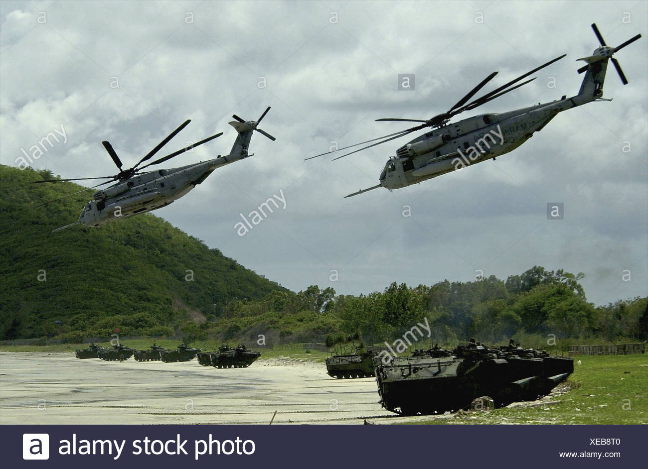 Helicopters fly over while amphibious vehicles land on a Thai beach during an assault demonstration Stock Photo