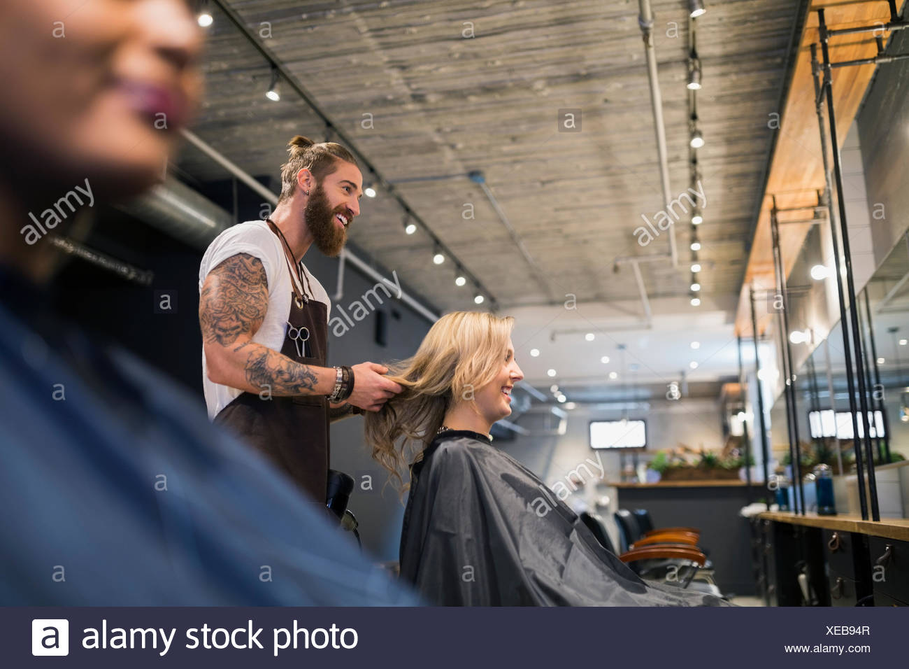 Male hairstylist styling womans hair in hair salon - Stock Image
