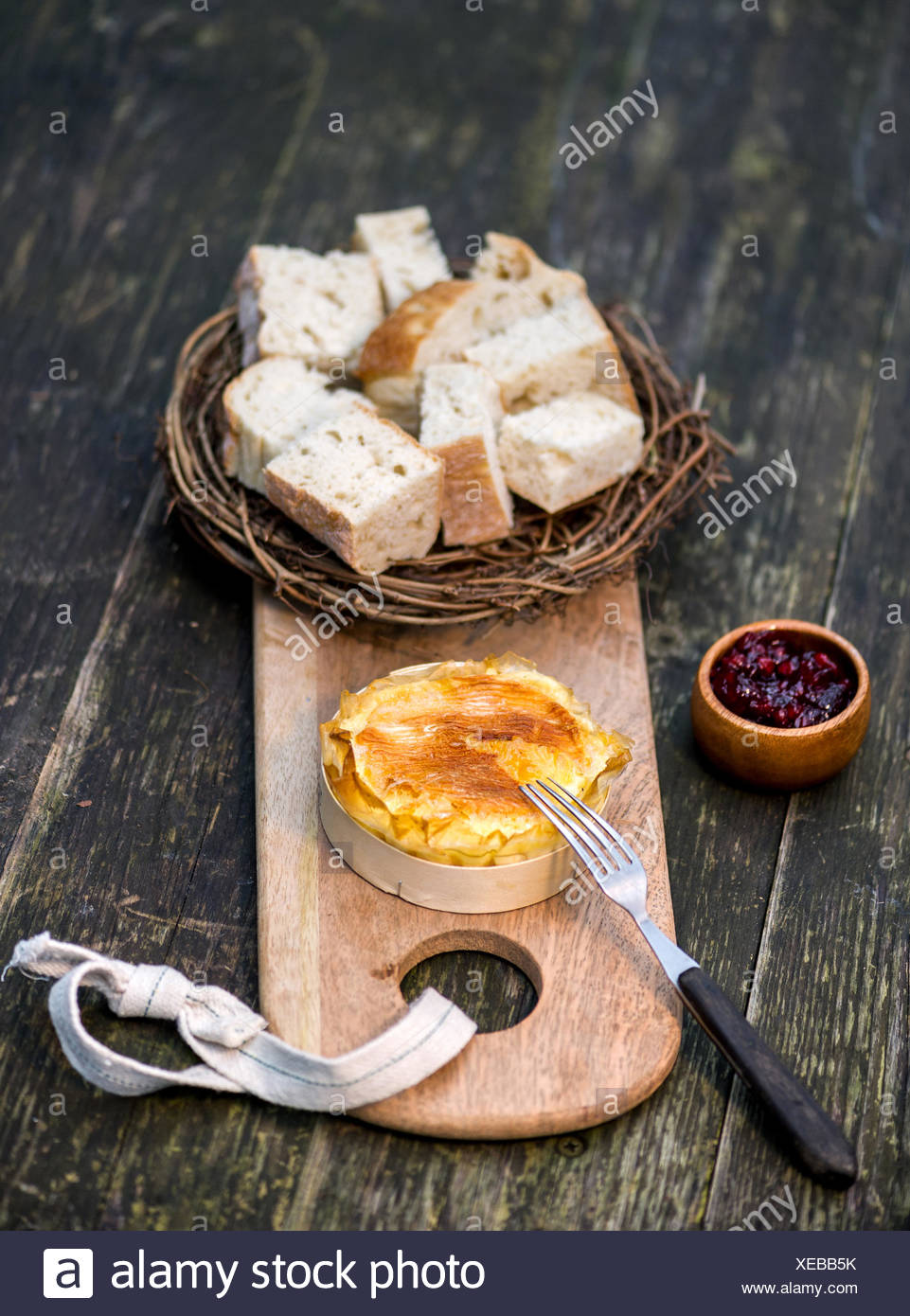 Camembert, served with a bread basket and cranberries - Stock Image