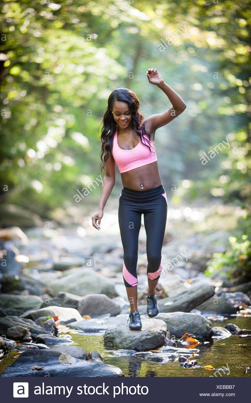 Young female hiker stepping across forest river rocks - Stock Image