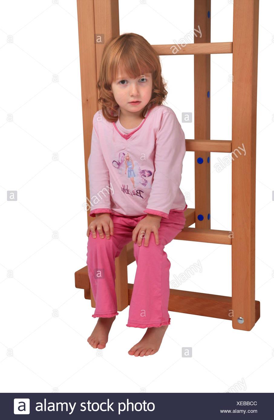 little girl in pyjama sitting on the ledder of a Billi-Bolli loft bed - Stock Image