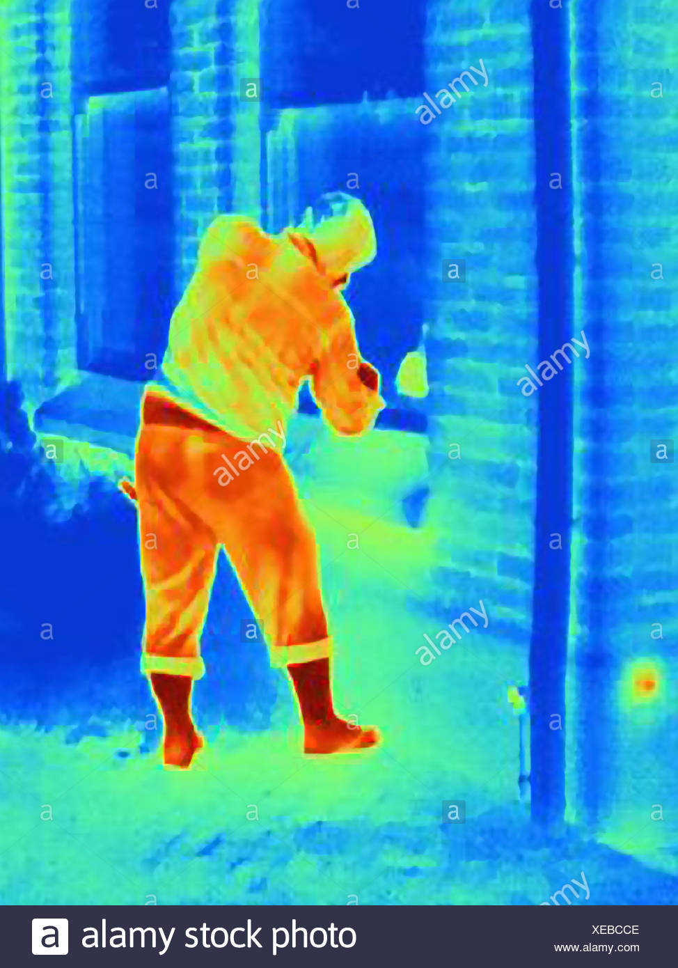 Thermal photograph of a burglar breaking into a house - Stock Image
