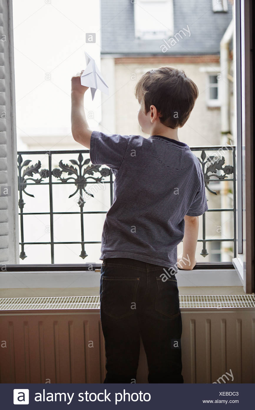Boy launching paper plane from window - Stock Image