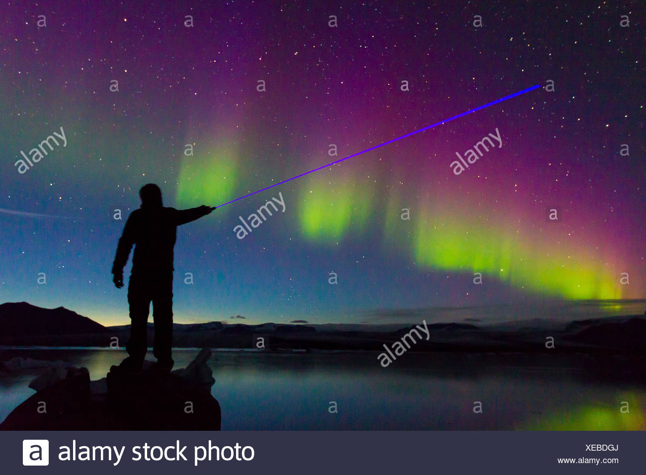 A man shining a blue laser at the Northern Lights during a geomagnetic solar storm so intense the lights reflecting off the freezing water. - Stock Image