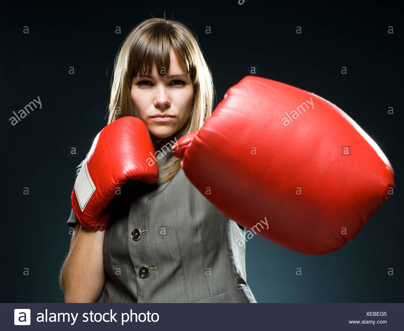businesswoman wearing boxing gloves - Stock Image