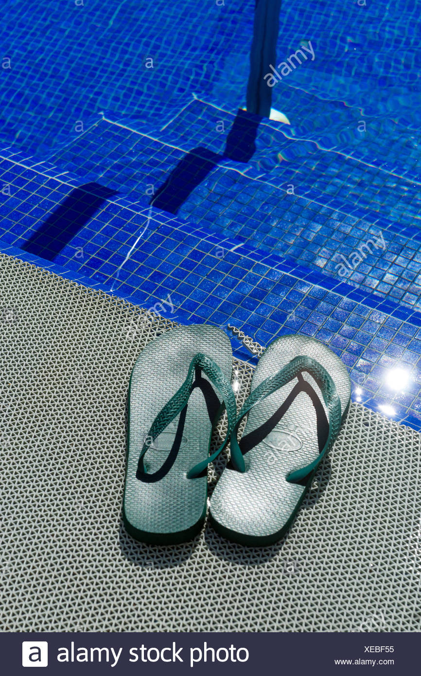 Green flip-flops at a pool - Stock Image
