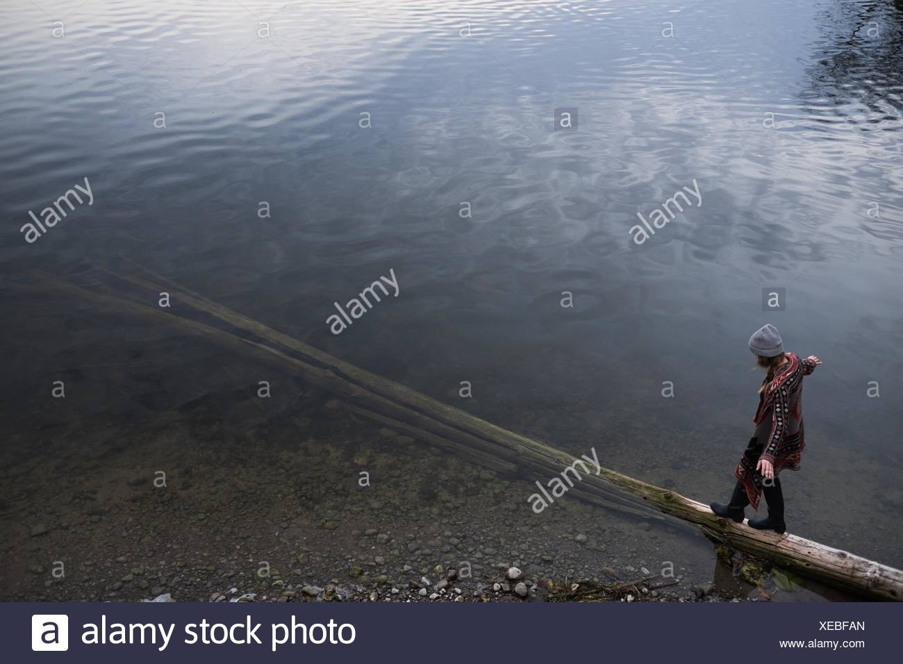 Woman balancing on fallen tree trunk in lake - Stock Image