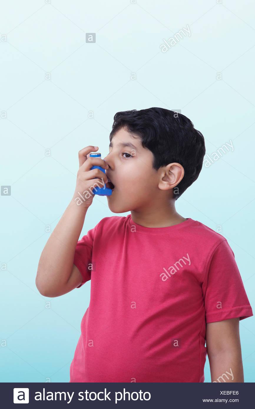 Asthmatic boy using an inhaler - Stock Image