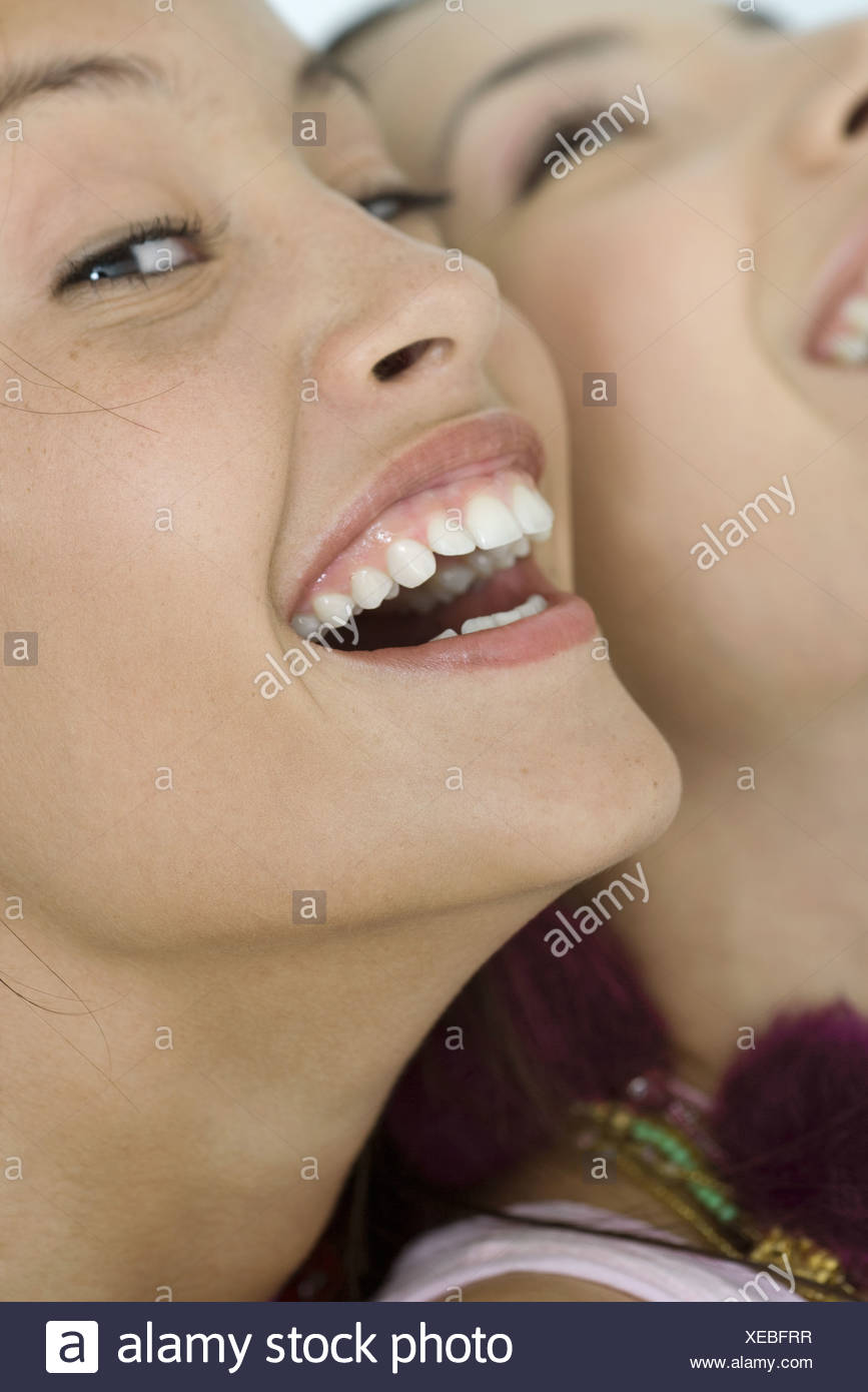 Two young female friends laughing, one looking at camera, extreme close-up of faces, cropped - Stock Image