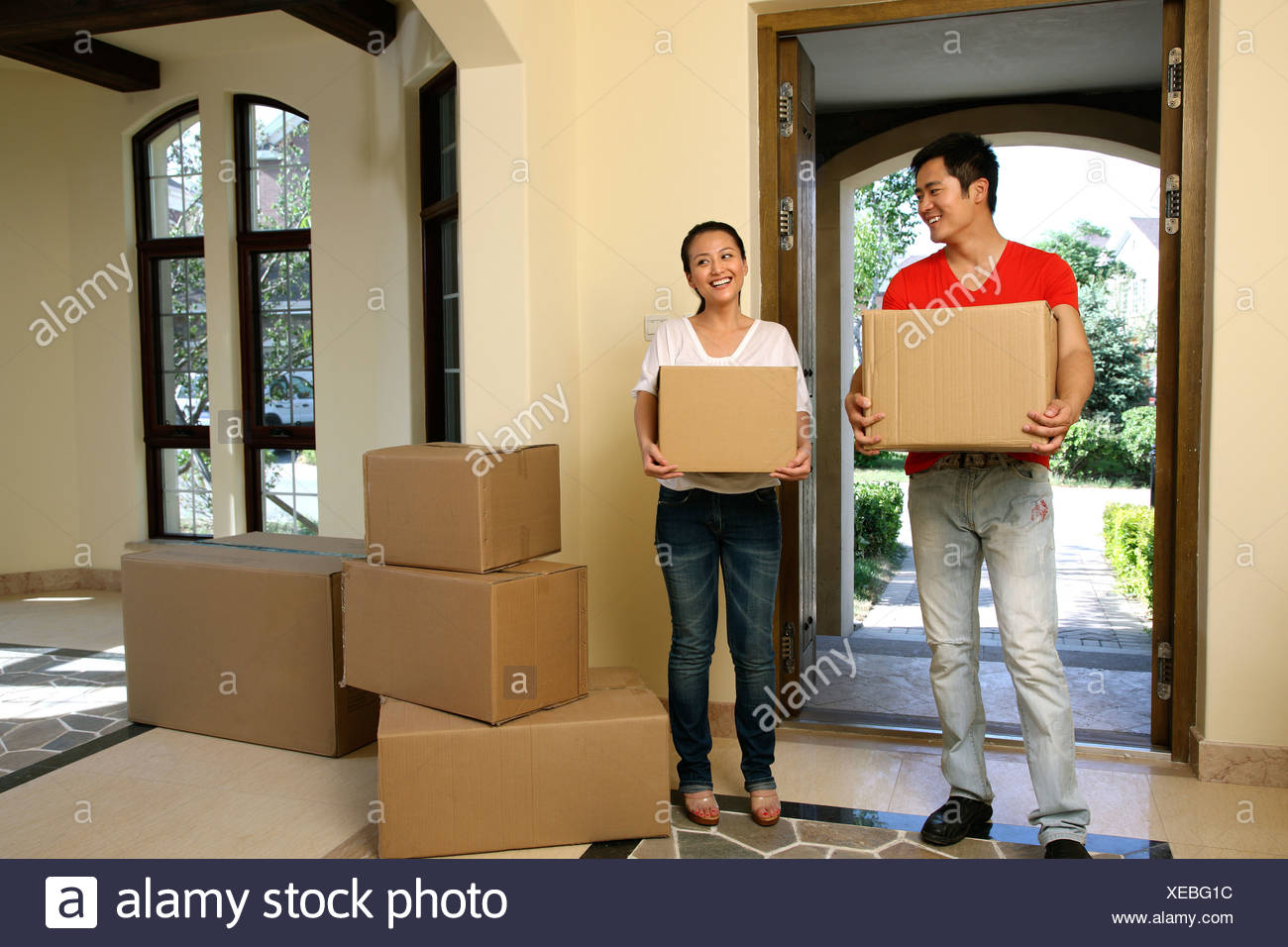 Chinese young couple moving into new home - Stock Image