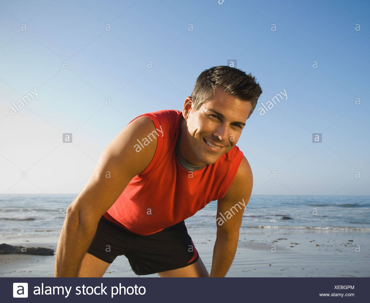 Man in athletic gear at beach - Stock Image
