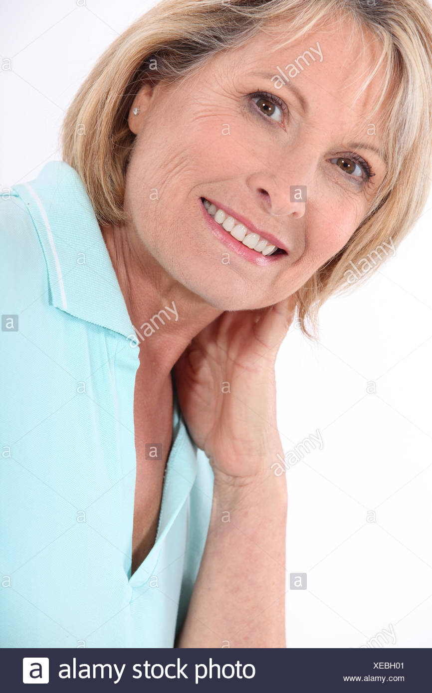 mature blonde woman wearing a turquoise polo shirt having a large smile - Stock Image