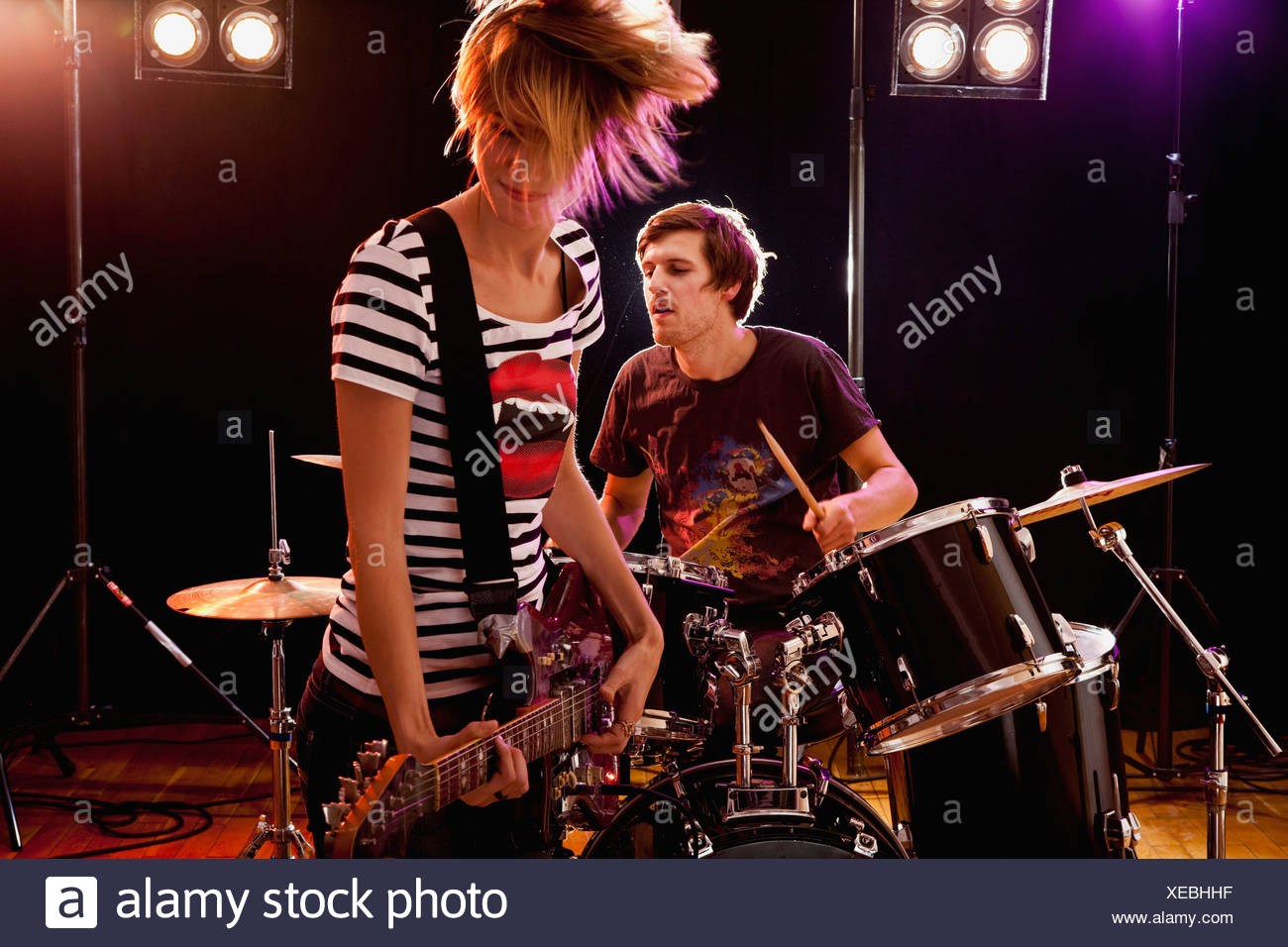 A man playing drums and a woman playing guitar in a rock band performing on stage - Stock Image