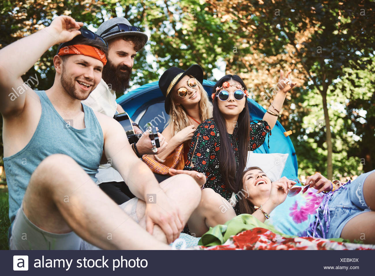 Five young adult friends playing acoustic guitar while festival camping - Stock Image