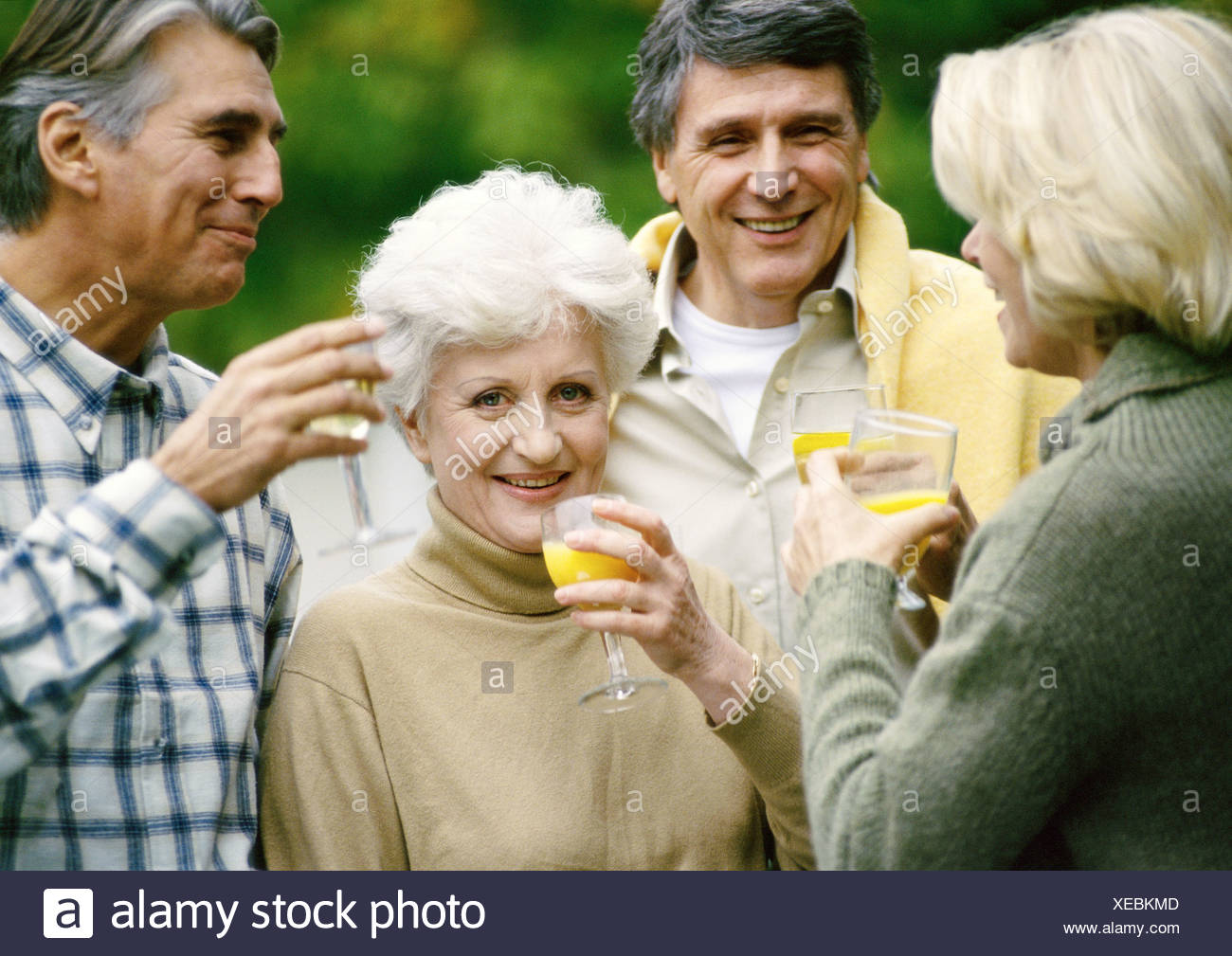 Mature people standing together with drinks in hands, close up - Stock Image